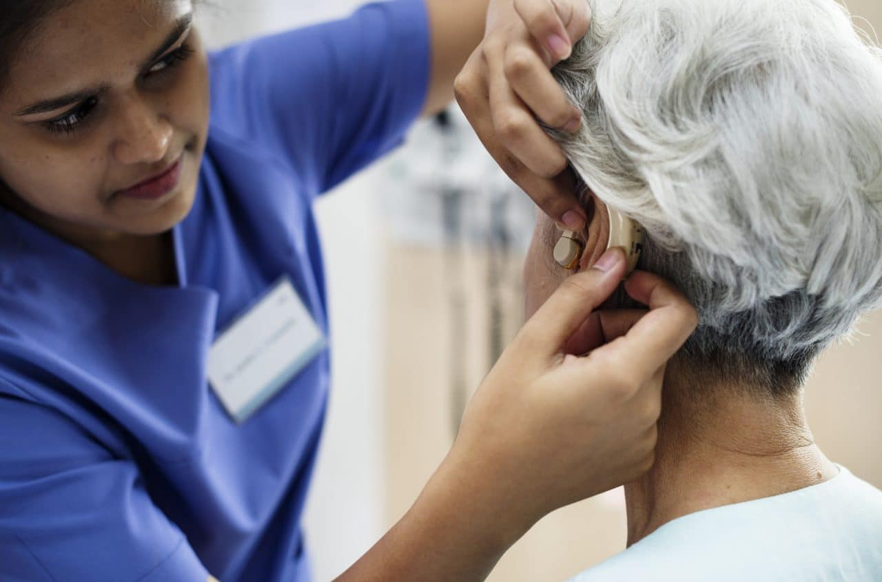 An audiologist fitting a woman with a new hearing aid.
