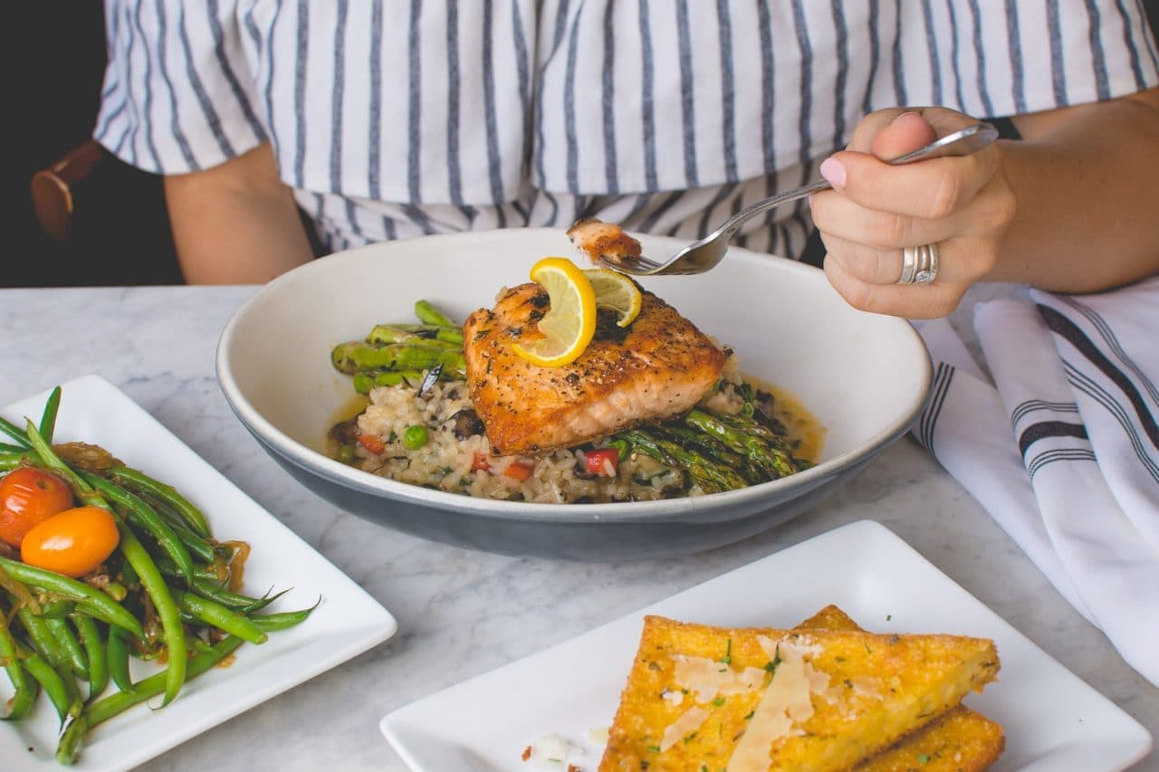 A person in front of a dinner plate of grilled fish and vegetables.